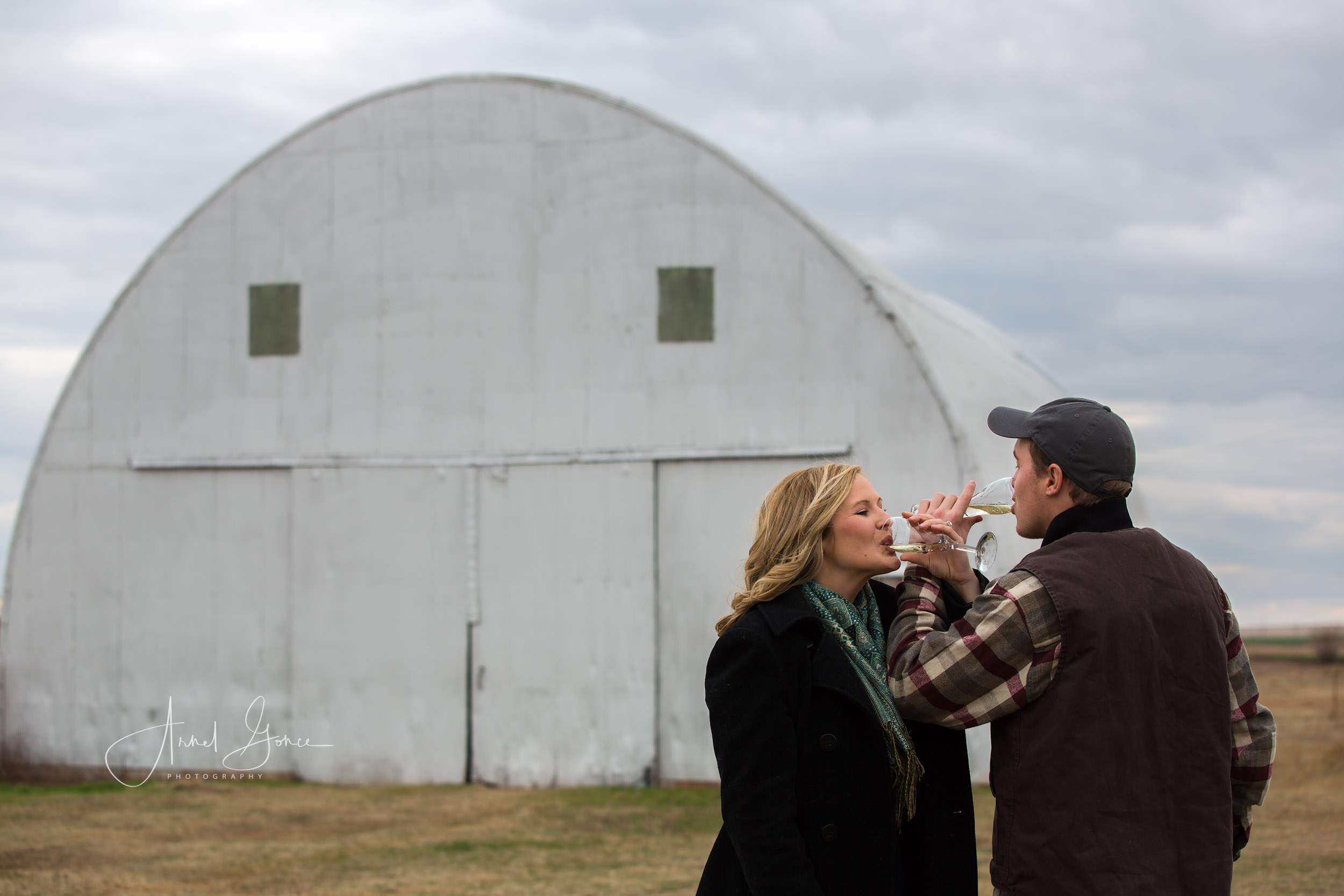 Bride and Groom to be standing in front of a barn on a farm in Piedmont Oklahoma drinking champagne.