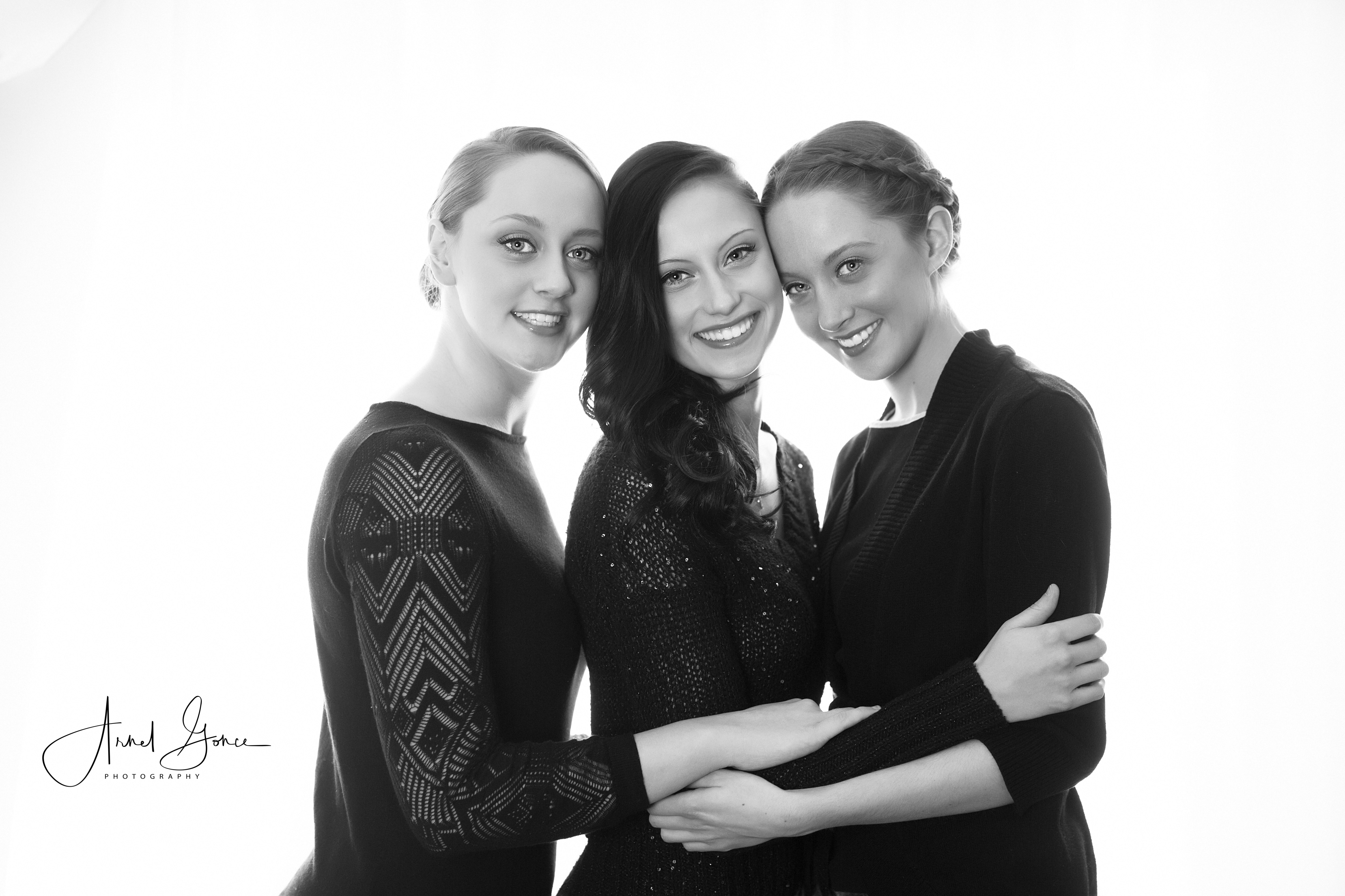 Black and white photography of three sisters hugging together for their portrait. Photograph backlit in front of large sliding glass door.