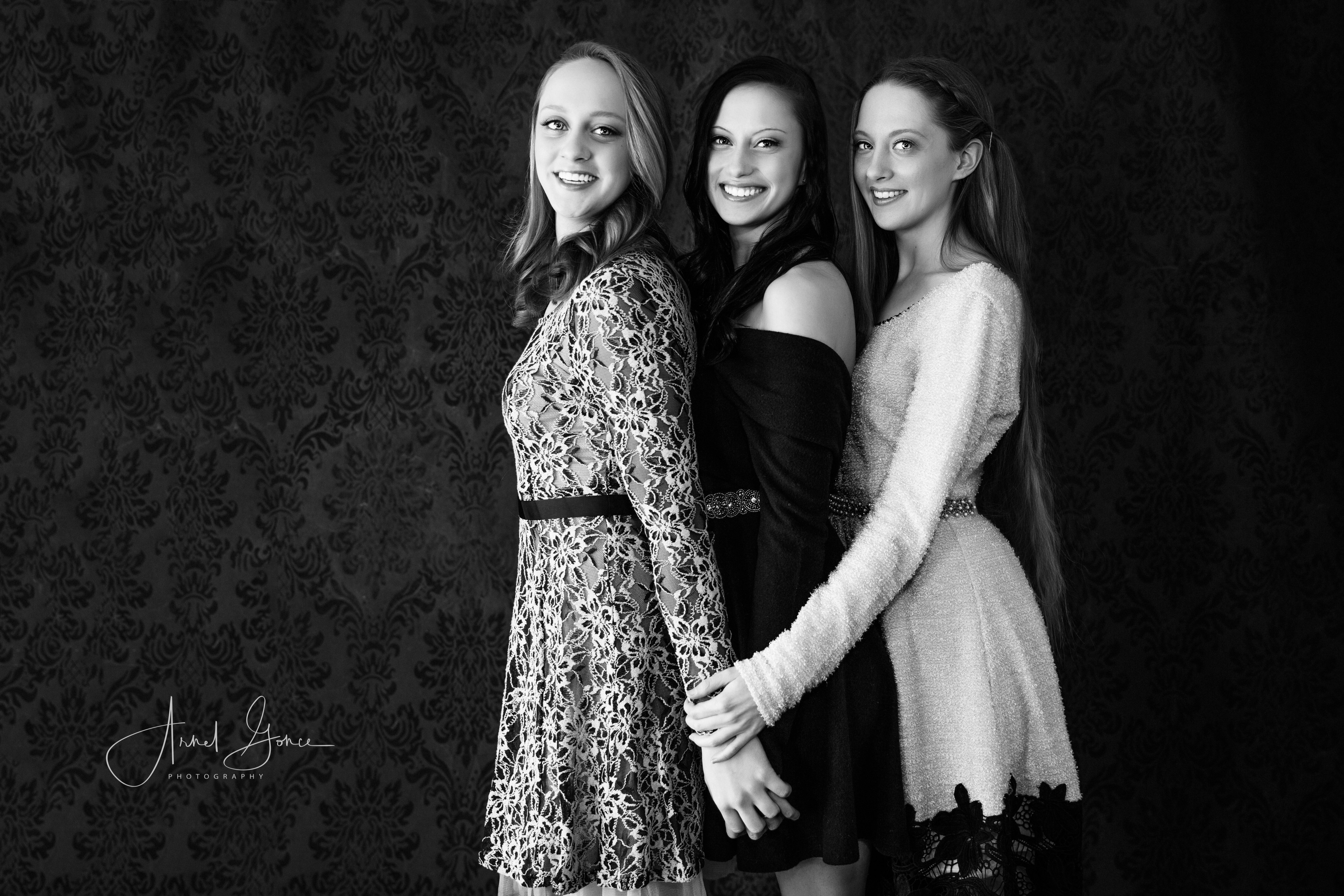 Black and white studio portrait photography session of three sisters. Subjects wearing Seasonal Party dresses by Altar'd States. Shot with a 5DMIII with a Canon 24-70MM L f/2.8 lens. Canvas backdrop with design. Shot by Arnel Gonce Photography Studio